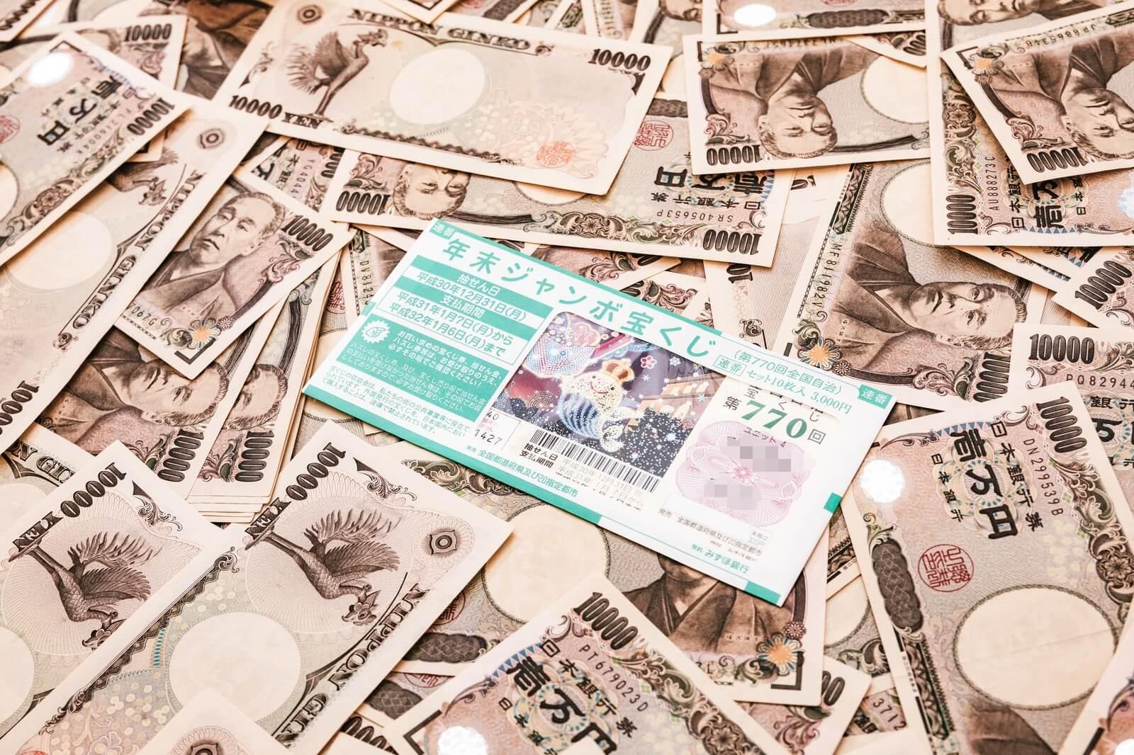 たくさんの一万円札と宝くじの画像